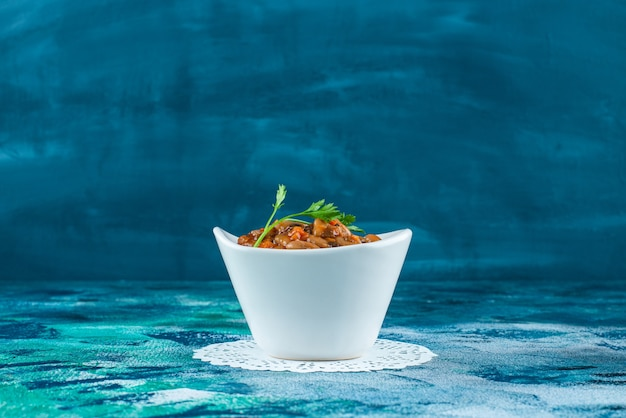 A bowl of baked beans on a coaster, on the blue background.
