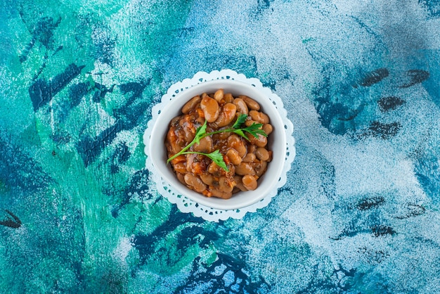 A bowl of baked beans on coaster on blue.