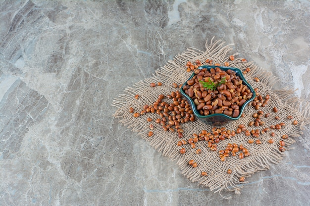 Bowl of baked beans on fabric on marble.