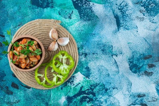Ciotola di fagioli al forno con prezzemolo accanto a aglio e pepe su un sottopentola, su sfondo blu.