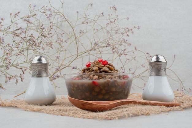 Ciotola di fagioli con semi di melograno e sale su tela.