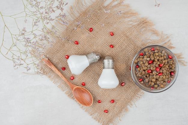Ciotola di fagioli con semi di melograno e sale su tela