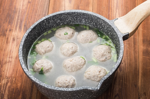 A bowl of beef ball soup on a wooden board background