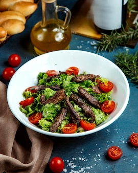 Bowl of beef salad with lettuce and cherry tomato