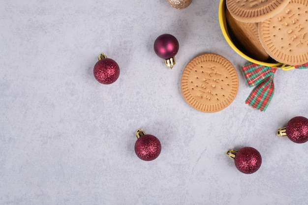 Bowl of biscuits and christmas balls on marble background. high quality photo