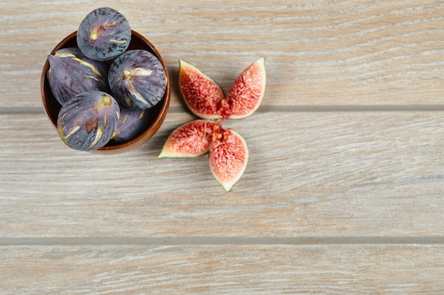 A bowl of black figs and slices of figs on a wooden table. high quality photo