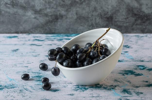 Bowl of black fresh grapes.