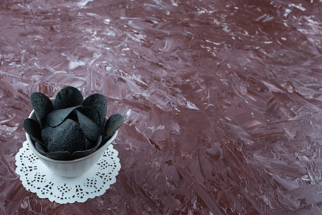 A bowl of black potato chips on coaster on marble.