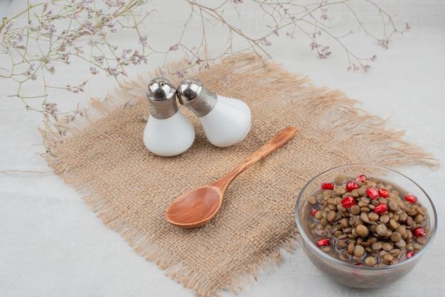 Ciotola di fagioli bolliti con semi di melograno sulla superficie bianca con sale.