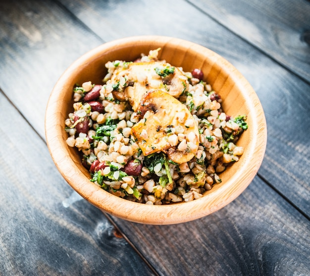 Bowl of boiled buckwheat with fried champignon, spinach and red beans