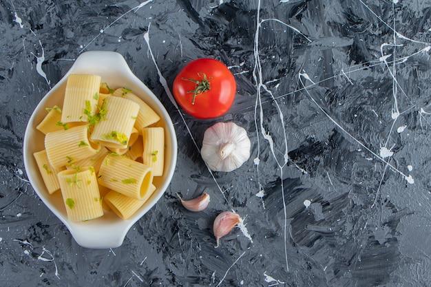 Ciotola di pasta calamarata bollita con verdure su priorità bassa di marmo.