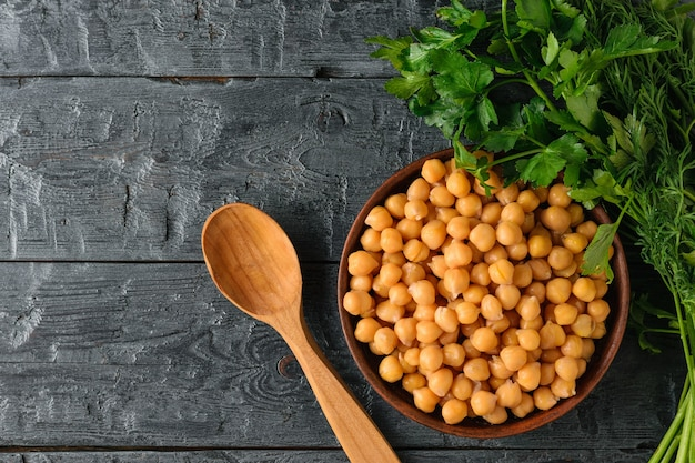 A bowl of boiled chickpeas, parsley and a wooden spoon on the rustic table.