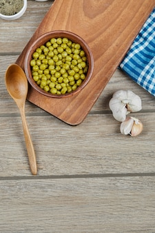 A bowl of boiled green peas with a spoon, garlic, and a blue tablecloth on a wooden table.