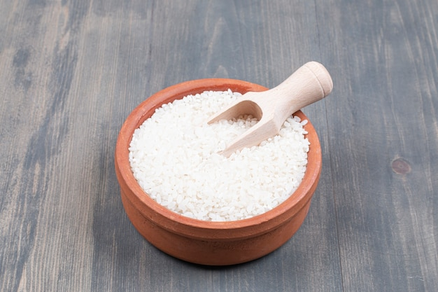 Bowl of boiled rice with spoon on wooden table