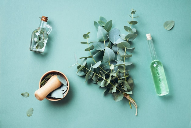 Bowl, bottles of eucalyptus essential oil, mortar, bunch of fresh eucalyptus branches