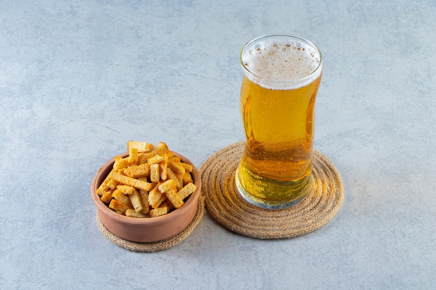 A bowl of breadcrumbs and beer in a glass on a trivet, on the marble surface.