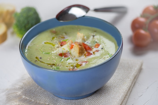 Bowl of broccoli cream soup, croutons with olive oil, vegetarian soup