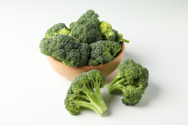 Bowl and broccoli on white surface. fresh vegetable