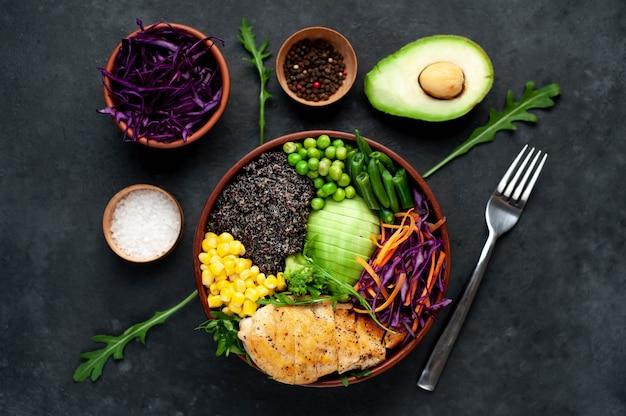 ボウルbuddha.quinoa、鶏の胸肉、ルッコラ、アボカド、赤キャベツ、ニンジン、グリーンピース、トウモロコシ、トマト、白いプレートに緑色の豆。