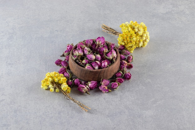 Bowl of budding roses and yellow flowers on stone background.