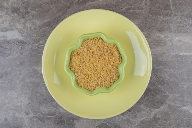 A bowl of bulgur on the plate ,on the marble surface
