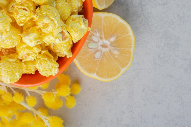 Bowl of caramel coated popcorn, lemon slice and a bundle of puffy flowers on marble surface