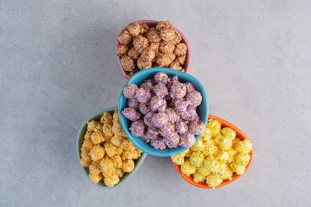 Una ciotola di popcorn ricoperti di caramello con due fette di limone accanto a un fascio di fiori gonfi su marmo.
