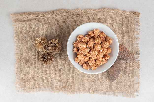 Bowl of caramel popcorn and a bunch of conifer cones on a piece of fabric on marble table.