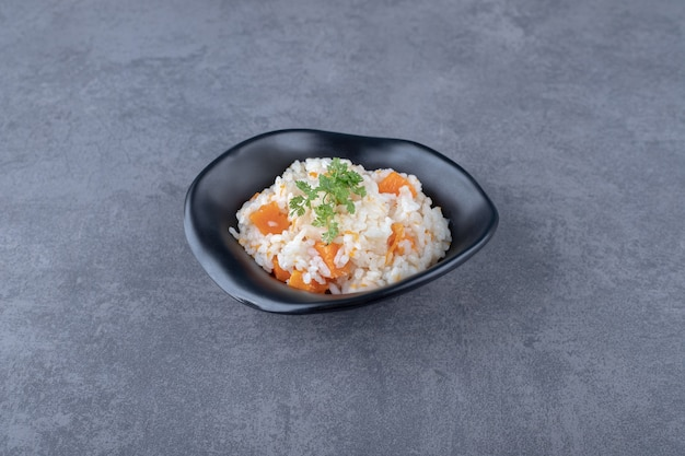 A bowl of carrot rice , on the marble surface.
