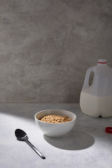 Bowl of cereal near a gallon of milk on a white table near a white wall