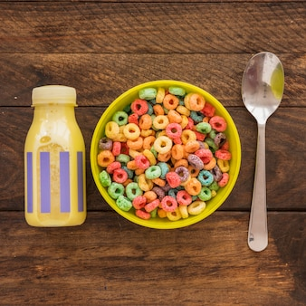 Bowl of cereal with bottle and spoon