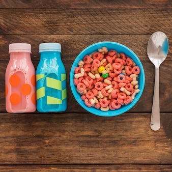 Bowl of cereal with two bottles and spoon
