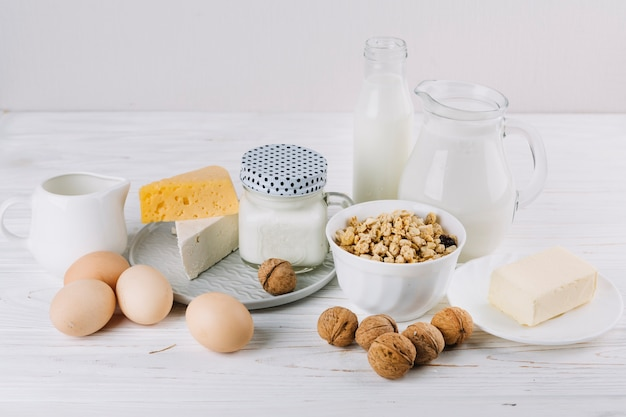Bowl of cereals; milk; eggs; cheese and walnuts on white textured backdrop