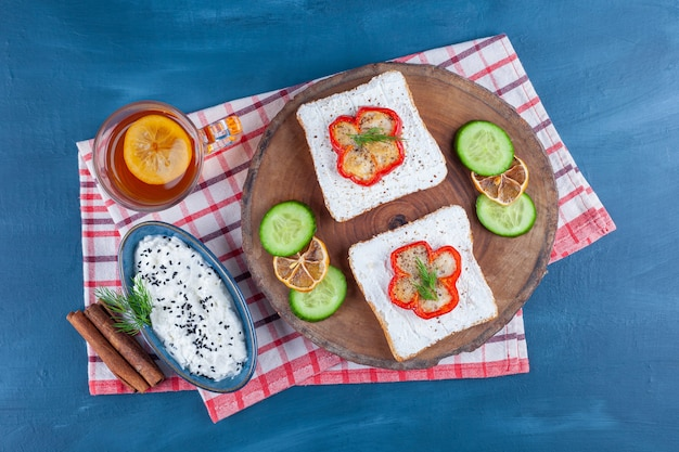 A bowl of cheese, a glass of tea next to cheese bread, sliced lemon and cucumber on a board , on the blue.