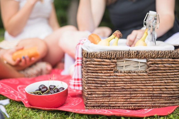 Bowl of cherry and picnic basket with people in the background