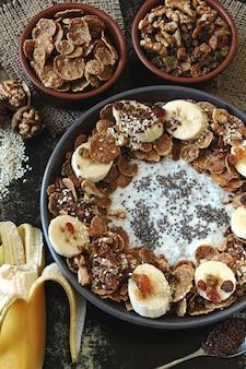 A bowl of chia yogurt, banana, seeds and cereal.