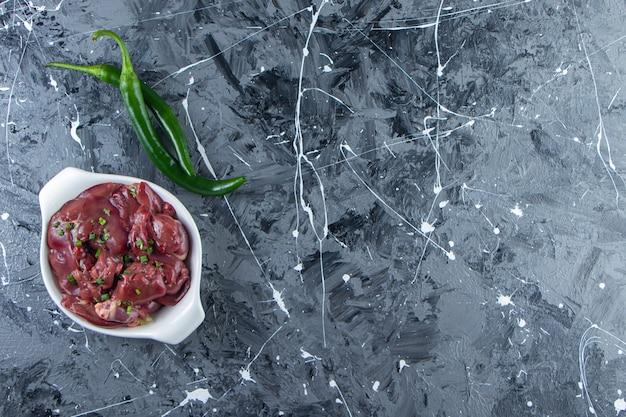 Una ciotola di frattaglie di pollo accanto al pepe, sullo sfondo di marmo.