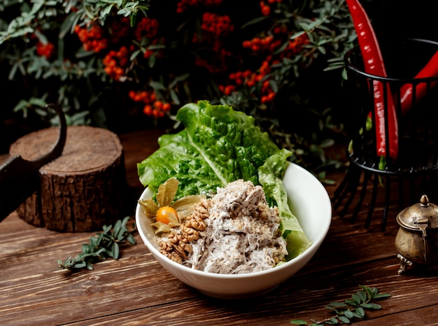 Bowl of chicken salad with walnut, plum and mayonnaise