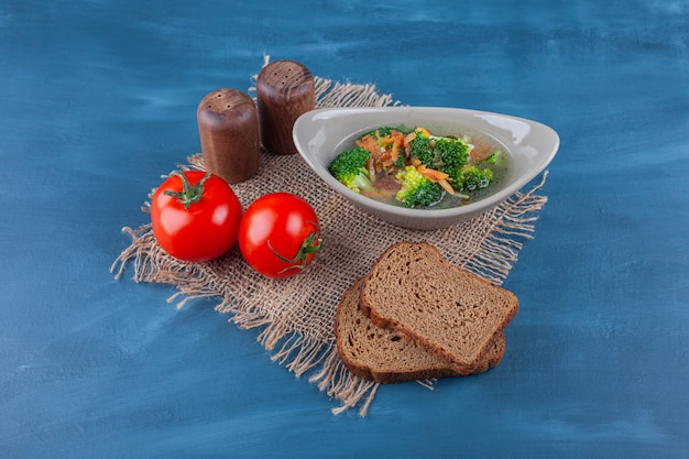 Bowl of chicken soup, vegetables, and bread on a burlap napkin on the blue surface