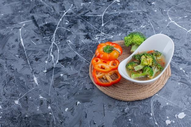 Ciotola di zuppa di pollo e verdure su un sottopentola, su sfondo blu.