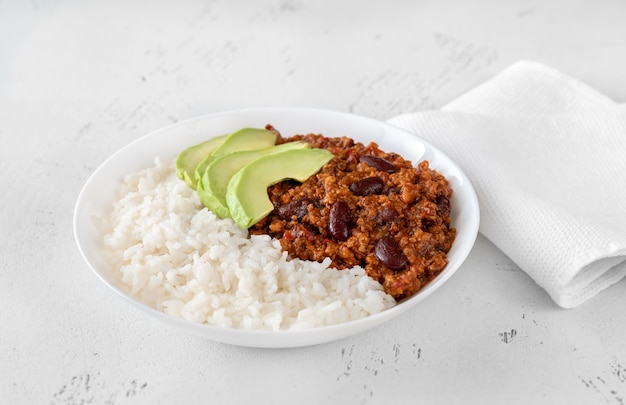 Bowl of chili con carne with rice, avocado and sour cream