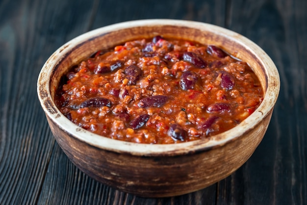 Bowl of chili con carne on wooden table