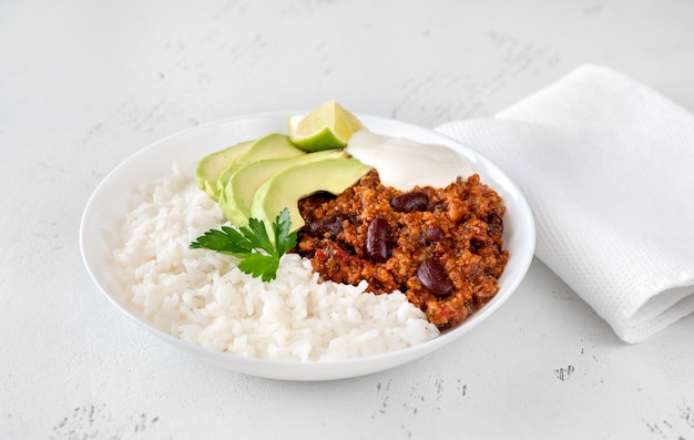 Bowl of chili with meat with rice, avocado and sour cream