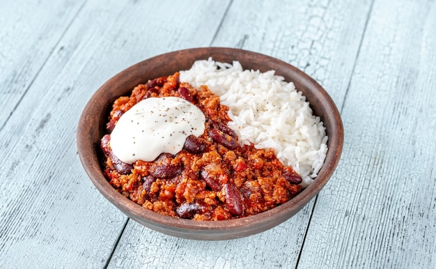 Bowl of chili with meat with rice and sour cream