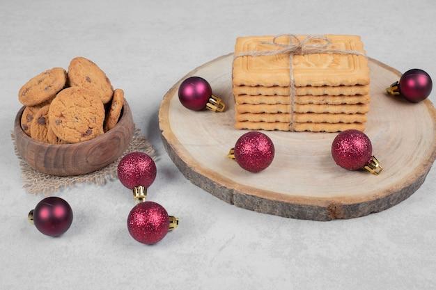 Ciotola di biscotti con patatine fritte, biscotti e palle di natale sul tavolo bianco. foto di alta qualità