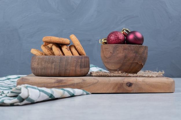 Ciotola di biscotti con patatine fritte e palle di natale sul tavolo bianco. foto di alta qualità