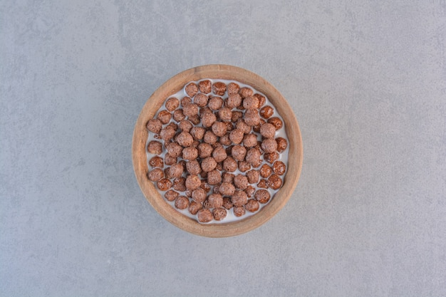 Bowl of chocolate cereal balls with milk on stone.
