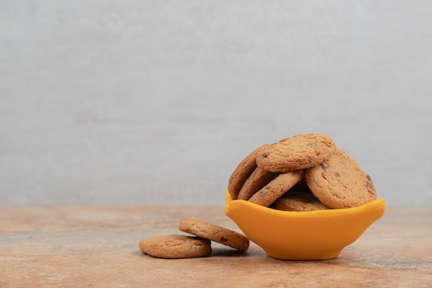 Bowl of chocolate chips cookies on marble background.