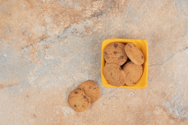 Ciotola di biscotti al cioccolato su sfondo marmo.