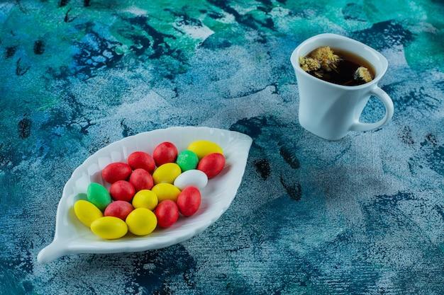 Ciotola di cioccolato e tazza di tè, su sfondo blu.